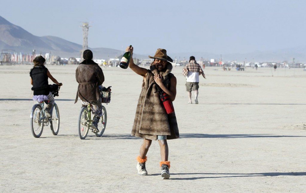 A Burning Man participant toasts the sunrise with a bottle of champagne at the 2013 Burning Man arts and music festival in the Black Rock desert of Nevada
